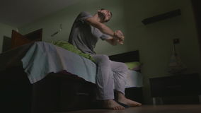 Young handsome man waking up getting out of bed and putting on slippers stock footage