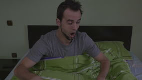 Young handsome man waking up scared stock video footage