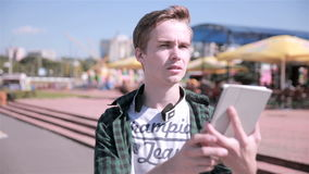 Young handsome man walking in the city with tablet, playing game. stock video