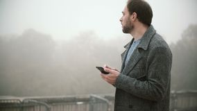 Young handsome man walking in foggy park in the morning. Bearded male using the smartphone with touchscreen. Attractive man browsing the Internet from mobile stock footage