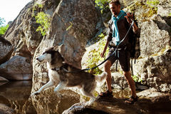 Young handsome man walking with huskies dog in canyon near water. Stock Images