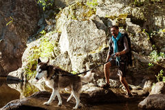 Young handsome man walking with huskies dog in canyon near water. Stock Image
