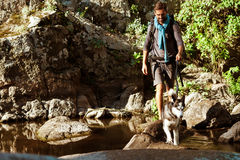 Young handsome man walking with huskies dog in canyon near water. Royalty Free Stock Photo