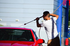 Young handsome man  washing car. Young handsome  tanned muscular man  washing his modern red   luxurious car outdoor Stock Photo