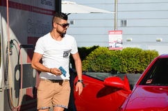 Young handsome man  washing car. Young handsome  tanned muscular man  washing his modern red   luxurious car outdoor Royalty Free Stock Photography