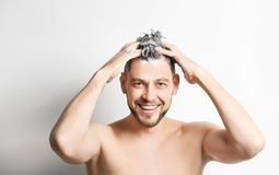 Young handsome man washing hair. On white  background Stock Photos