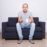 Young handsome man watching tv with cup of tea Royalty Free Stock Image