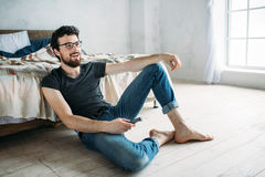 Young handsome man watching TV on a floor at home. Bearded guy in glasses in black shirt and jeans smiling while watching talk show Royalty Free Stock Photography