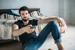 Young handsome man watching TV on a floor at home. Cute guy in black shirt and blue jeans looking at the screen and holding remote control Stock Photos