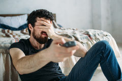 Young handsome man watching TV on a floor at home. Emotional guy closing his face with left hand, He can`t see his team loosing. Close up Stock Photography