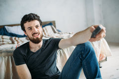 Young handsome man watching TV on a floor at home. This guy having some rest but he is unsatisfied because he can`t find nothing worth to watch. Close up Stock Images