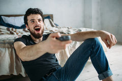 Young handsome man watching TV on a floor at home. Nice guy is amazed because of watching some strange TV programme. Close up Royalty Free Stock Images