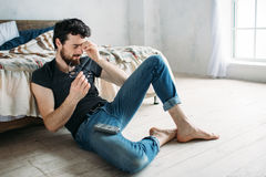 Young handsome man watching TV on a floor at home. Tired guy is rubbing his nose bridge, he has headache from the galasses Stock Images