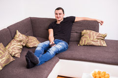 Young handsome man watching TV on a sofa at home Stock Images