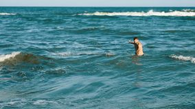 Young handsome man waving sea algae weed plant sea beach blue water polution environment element earth waves sunny stock footage