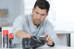 Young handsome man waxing shoes. Young handsome man waxing his shoes Royalty Free Stock Photos