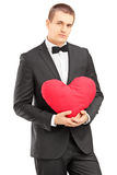 Young handsome man wearing black suit and holding a red heart. Isolated on white background Stock Photo