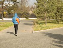 Young handsome man wearing a blue jacket with a sports bag, walking in Park, rear view.  Royalty Free Stock Photography