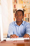 Young handsome man wearing blue office shirt sitting by computer desk typing and looking uninspired Royalty Free Stock Image