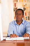 Young handsome man wearing blue office shirt sitting by computer desk typing and looking uninspired Royalty Free Stock Photos