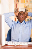 Young handsome man wearing blue office shirt sitting by computer leaning backwards in chair holding head in disbelief Royalty Free Stock Images