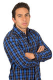 Young handsome man wearing a blue plaid shirt. Young serious handsome man wearing a blue plaid shirt posing with arms crossed isolated on white Royalty Free Stock Photography