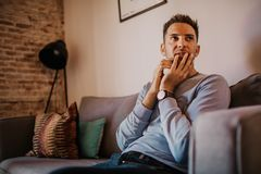 Young handsome man wearing casual clothes relaxing on sofa at modern apartment. Young handsome man wearing casual clothes relaxing on sofa at modern apartment stock photography