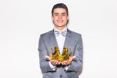 Young handsome man wearing with crown in hands suit  looking at camera Stock Image