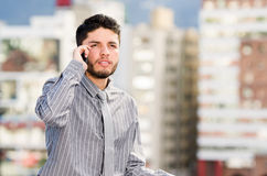 Young handsome man wearing shirt and tie standing on rooftop, holding mobile phone talking while staring past camera. City buildings background Stock Photo