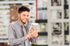 Young handsome man wearing shirt and tie standing on rooftop, holding tablet staring at screen, city buildings. Background Royalty Free Stock Images