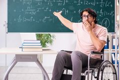 The young handsome man in wheelchair in front of chalkboard stock image