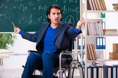 The young handsome man in wheelchair in front of chalkboard royalty free stock image