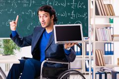 The young handsome man in wheelchair in front of chalkboard stock photo