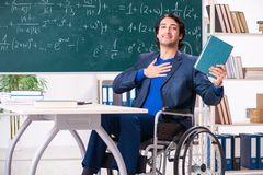 The young handsome man in wheelchair in front of chalkboard royalty free stock photography