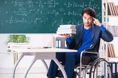 The young handsome man in wheelchair in front of chalkboard. Young handsome man in wheelchair in front of chalkboard royalty free stock image