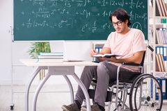 The young handsome man in wheelchair in front of chalkboard. Young handsome man in wheelchair in front of chalkboard royalty free stock photos