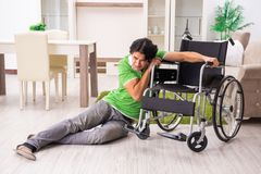 The young handsome man in wheelchair at home stock photos