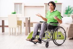 The young handsome man in wheelchair at home royalty free stock photo