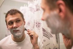 Young handsome man in white t-shirt shaves in front of bathroom mirror in the morning. stock photos