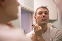 Young handsome man in white t-shirt shaves in front of bathroom mirror in the morning. stock images