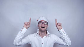 Young handsome man in white shirt and santa hat showing copy space above. stock video