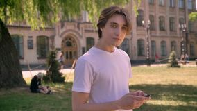 Young handsome man in white shirt typing on smartphone and looking at camera, student standing in park near university.  stock footage