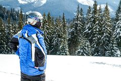 Young handsome man in winter sportswear looking away, wearing big mirrored ski mask.  Royalty Free Stock Photos