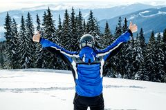 Young handsome man in winter sportswear looking away, wearing big mirrored ski mask.  Royalty Free Stock Images