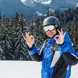 Young handsome man in winter sportswear looking away, wearing big mirrored ski mask. Man in blue ski suit looks at camera and smiles Royalty Free Stock Image