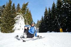 Young handsome man in winter sportswear looking away, wearing big mirrored ski mask. A man in a blue ski suit is sitting on the snow on top of a mountain Stock Photography