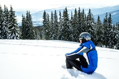 Young handsome man in winter sportswear looking away, wearing big mirrored ski mask. A man in a blue ski suit is sitting on the snow on top of a mountain Royalty Free Stock Photo