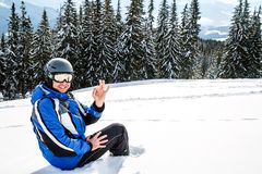 Young handsome man in winter sportswear looking away, wearing big mirrored ski mask. A man in a blue ski suit is sitting on the snow on top of a mountain Royalty Free Stock Photography