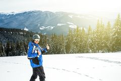 Young handsome man in winter sportswear looking away, wearing big mirrored ski mask. Man in blue ski suit looks at camera and smiles Royalty Free Stock Photography