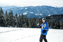 Young handsome man in winter sportswear looking away, wearing big mirrored ski mask. Man in blue ski suit looks at camera and smiles Stock Photography